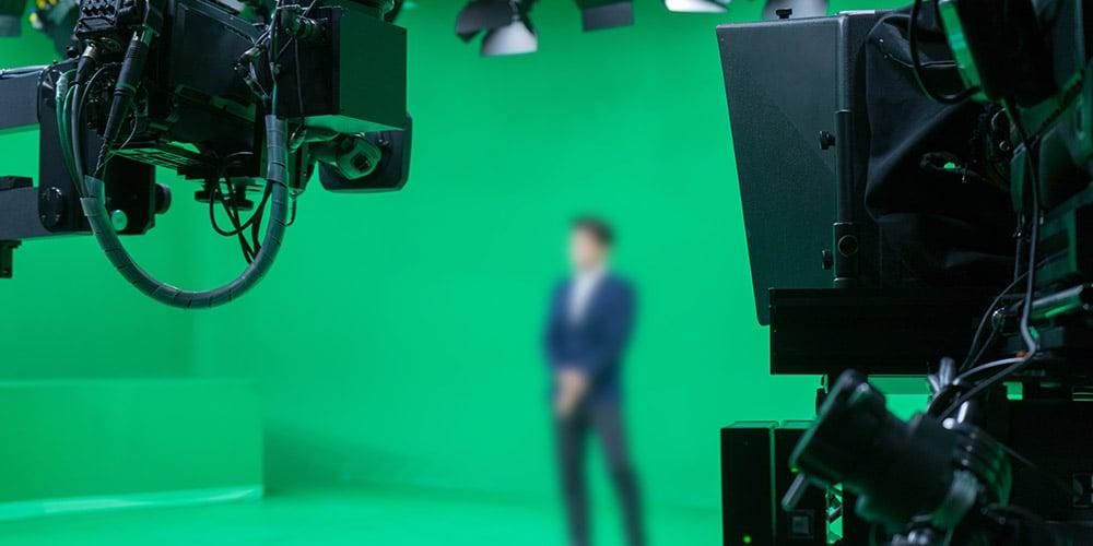 Presentator staat in een lege studio voor een greenscreen